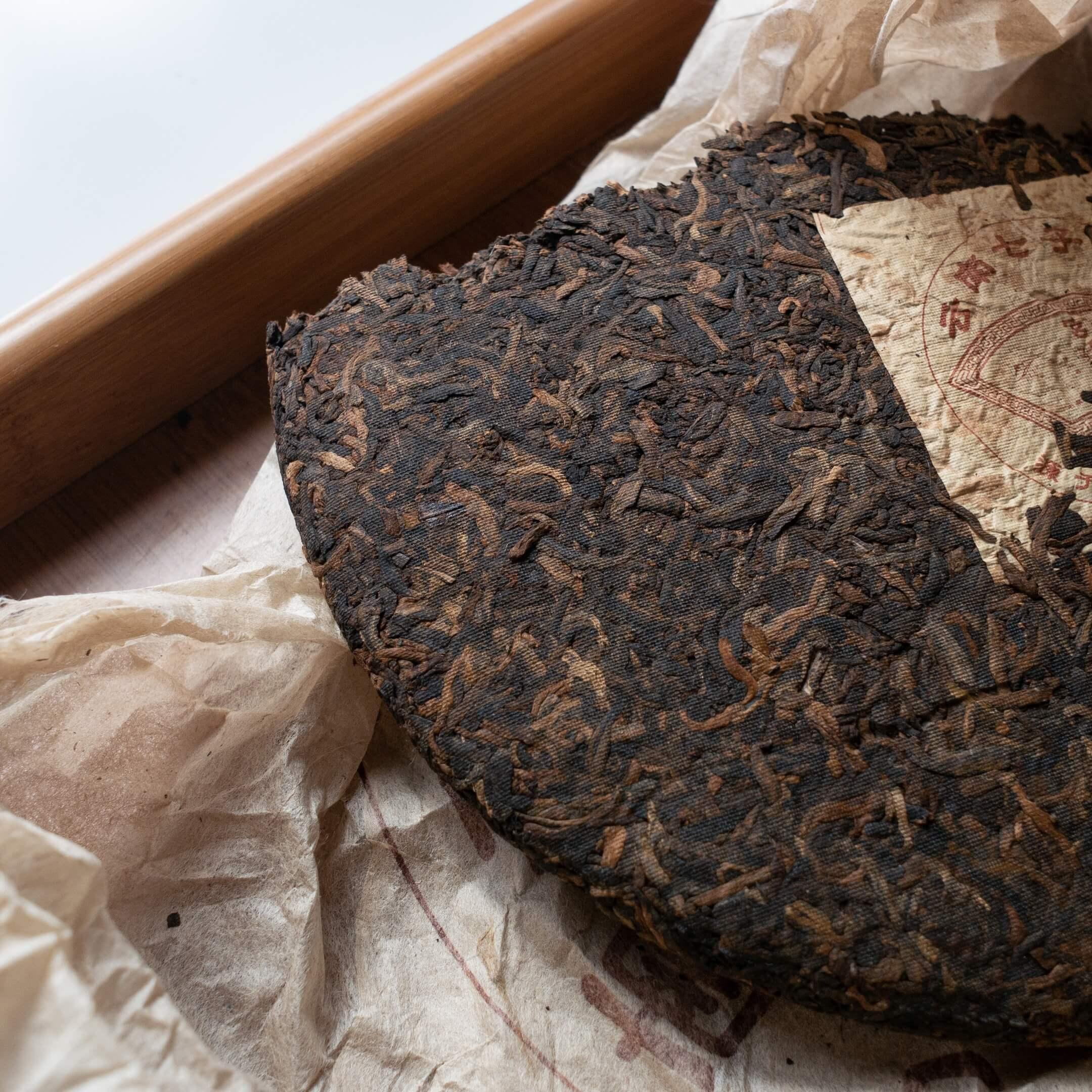 Чай пуэр в форме блина. Золотистые — чайные почки. Черные — листья.